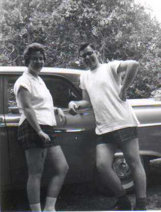 woman and man lean on 1950s car