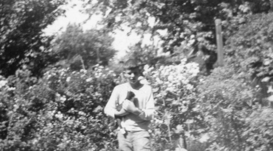 boy holds cat in garden