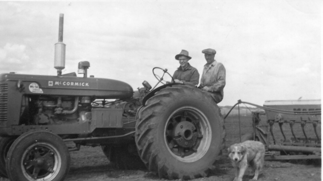 Two men and a dog with a McCormick tractor 1950s