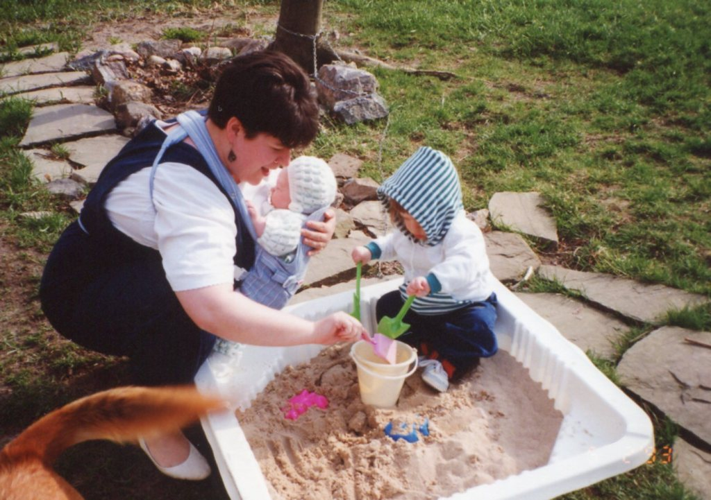 holding my baby and bending to play in the sandbox with my toddler